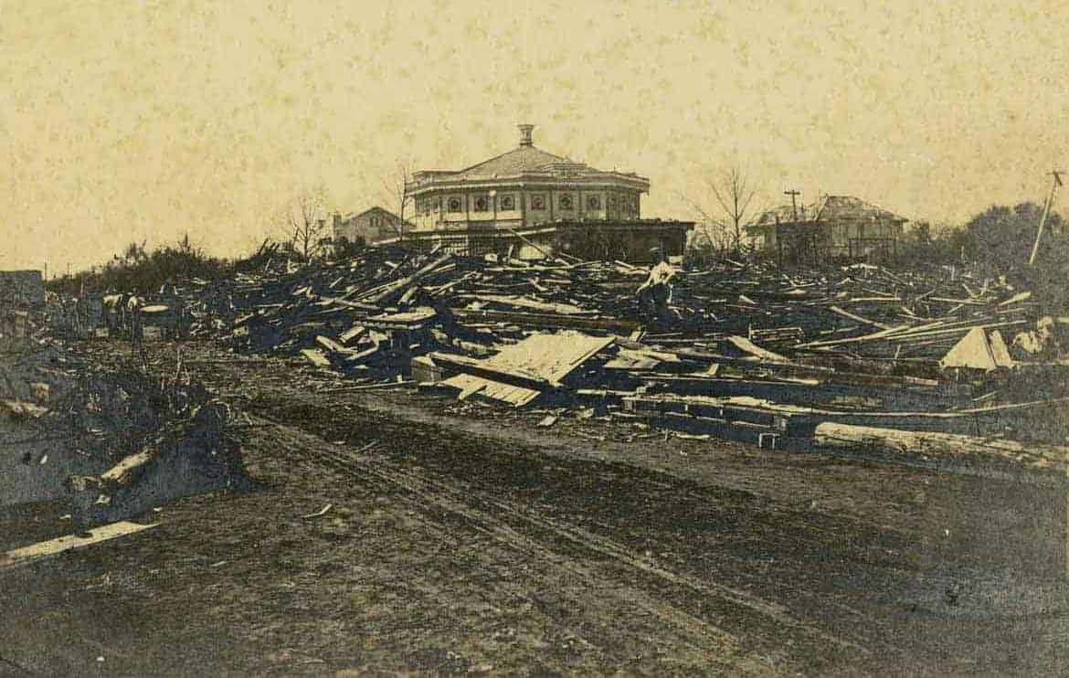 Piles of debris near the Garten Verein dancing pavilion after the 1900 Storm, corner of Avenue O and 27th Street looking northwest